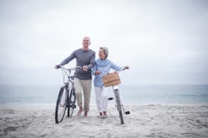 Senior couple on the beach with bikes