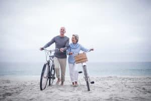 Senior couple on the beach with bikes