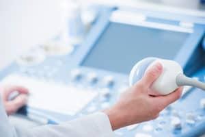 Close up of technician's hands operating a vascular ultrasound